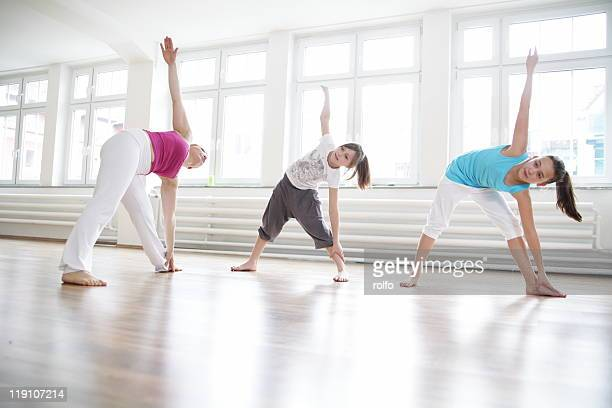 Yoga teacher stretching with two girls