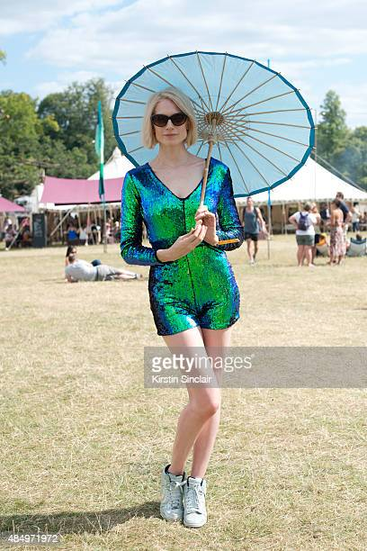 Yoga Teacher Tuuli Shipster wears Nike Trainers Tom Ford sunglasses an American vintage jumpsuit and a parasol from The Brolly company on day 2 of...