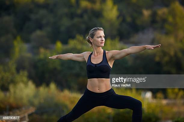 yoga teacher, virabhadrasana ii (warrior ii pose) - bra top stock pictures, royalty-free photos & images