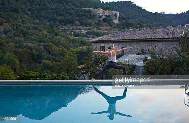 yoga teacher, virabhadrasana ii (warrior ii pose) - klaus vedfelt mallorca stock pictures, royalty-free photos & images