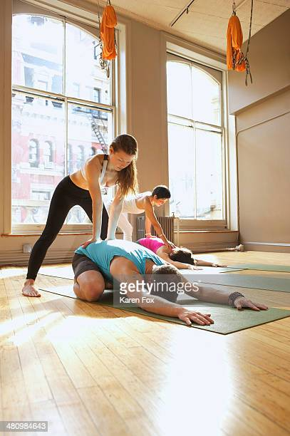 Yoga teachers assisting people in class
