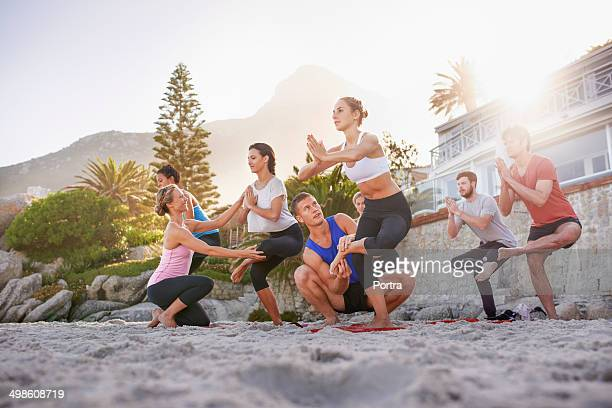 Yoga teachers helping their students