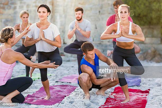 Yoga trainers helping in a class on the beach.