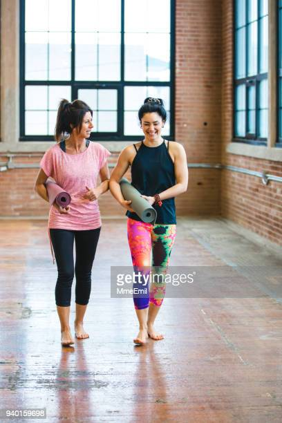 yoga training class preparation. two women having a conversation - yogi stock photos and pictures
