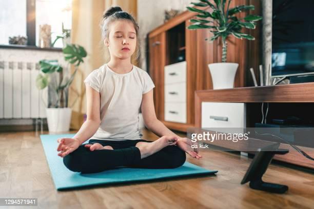 allenamento yoga online. ragazza carina a casa con tablet digitale in posizione lotus - fotografia immagine foto e immagini stock