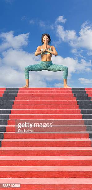 Yoga woman posing outdoors on red stairway