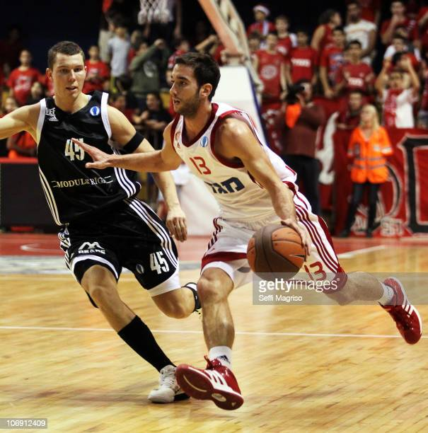 Yogev Ohayon #13 of Hapoel Jerusalem competes with Dairis Bertans #45 of VEF Riga during the Eurocup Basketball date 1 game between Hapoel Jerusalem...