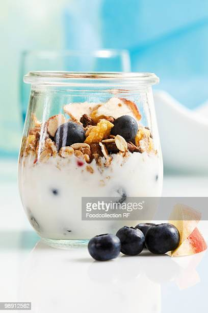 Yoghurt with muesli, blueberries, apple and dried fruit in jar, close-up