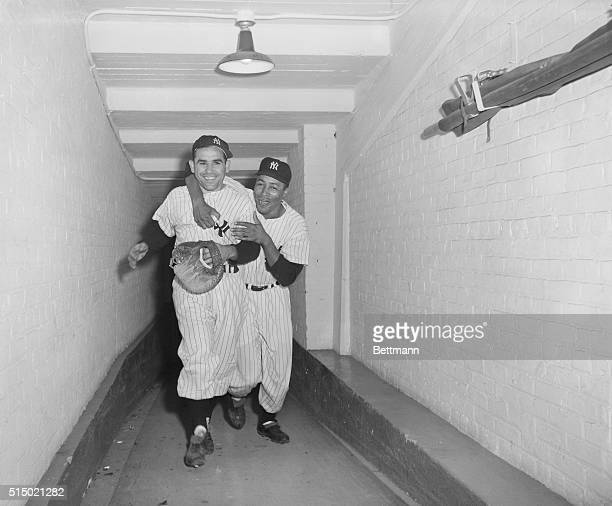 Yogi Berra is hugged by teammate Elston Howard following Berra's ninth-inning walk-off home run against the Boston Red Sox, defeating them at Yankee...