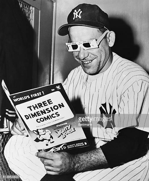 Yogi Berra of the New York Yankees a longtime enthusiast of comic magazines seems particularly pleased with a new type of funny book given him by the...