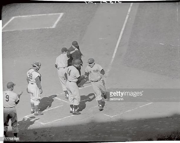 Yogi Berra of the Yankees is scoring on his first inning homer in the last game of the World Series at Ebbets Field He drove Bauer in ahead of him to...