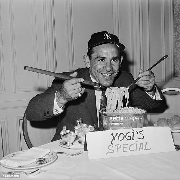Yogi Berra playfully digs into a pot of spaghetti for photographers during a press luncheon where he was named the Yankees' new manager The former...