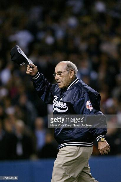 Yogi Berra tips his hat to the crowd after throwing out the ceremonial first ball before Game 7 of the American League Championship Series between...