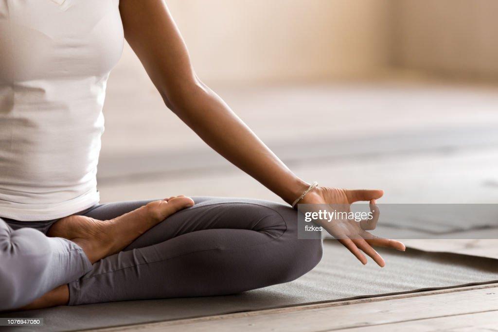 Yogi black woman practicing yoga lesson, doing Ardha Padmasana exercise : Stock Photo