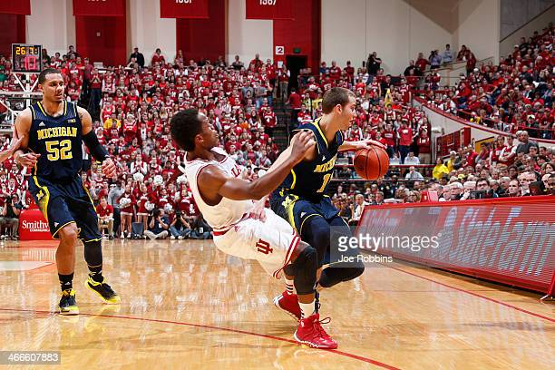 Yogi Ferrell of the Indiana Hoosiers draws a charging foul against Nik Stauskas of the Michigan Wolverines during the game at Assembly Hall on...