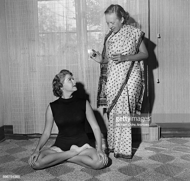 Yogi Indra Devi instructs a student on a yoga position in her studio in HollywoodCalifornia