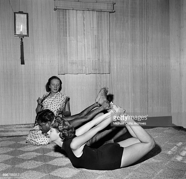 Yogi Indra Devi instructs her students on a yoga position in her studio in HollywoodCalifornia