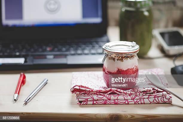 Yogurt breakfast on desk with laptop