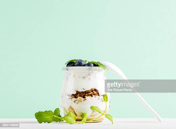 Yogurt oat granola with fresh berries and mint leaves in glass jar on grey concrete textured backdrop