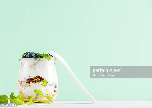 Yogurt oat granola with jam and blueberries in glass jar on mint pastel background