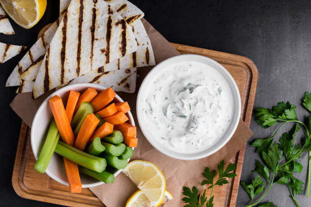 yogurt sauce with parsley served with fresh carrot and celery sticks - greek food stock photos and pictures