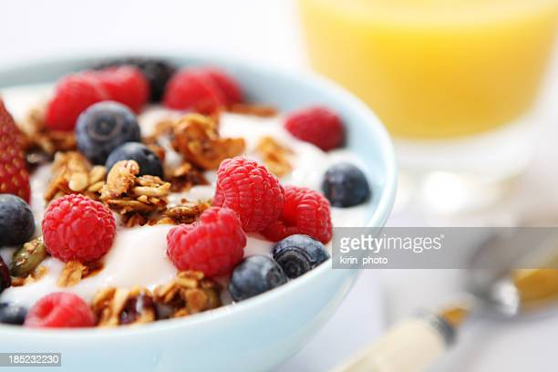 Yogurt with fresh berries and granola served in a white bowl