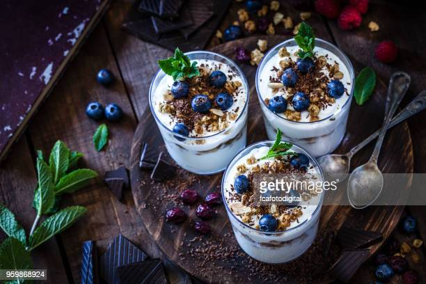 yogurt with granola, berry fruits and chocolate - sweet food stock pictures, royalty-free photos & images