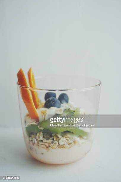 Yogurt With Muesli And Fruits In Glass On White Background