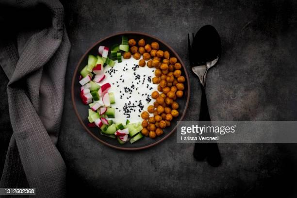 yogurt with spicy turmeric chickpeas and cucumber radish salad - larissa veronesi stock-fotos und bilder