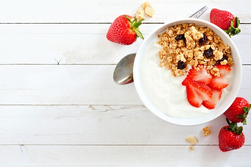 Yogurt with strawberries & granola, flat lay, side orientation over white wood. 912311154