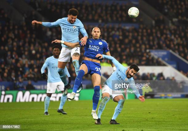 Yohan Benalouane of Leicester City jumps between Kyle Walker and Ilkay Gundogan of Manchester City during the Carabao Cup QuarterFinal match between...