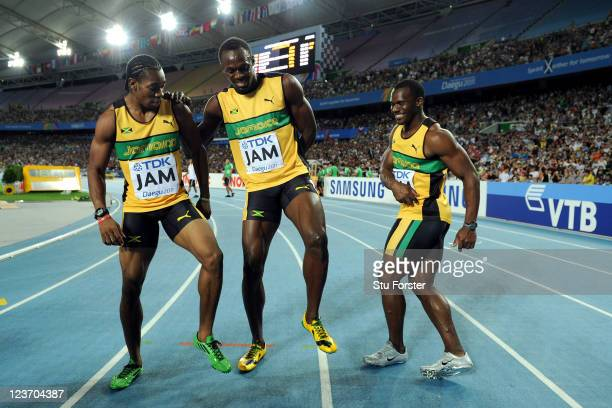 Yohan Blake, Usain Bolt and Nesta Carter of Jamaica celebrate victory and a new world record in the men's 4x100 metres relay final during day nine of...