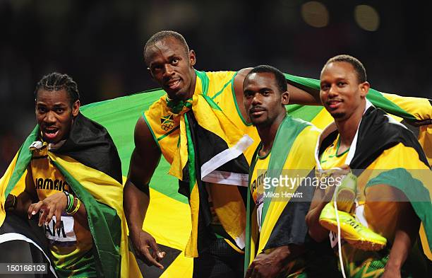 Yohan Blake, Usain Bolt, Nesta Carter and Michael Frater of Jamaica celebrate next to the clock after winning gold and setting a new world record of...