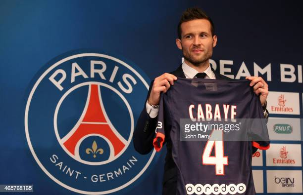 Yohan Cabaye is presented by Nasser AlKhelaifi president of Paris SaintGermain as a new player of PSG during a press conference with a jersey...