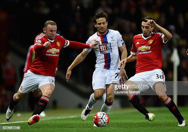 Yohan Cabaye of Crystal Palace is tackled by Wayne Rooney and Matteo Darmian of Manchester United during the Barclays Premier League match between...