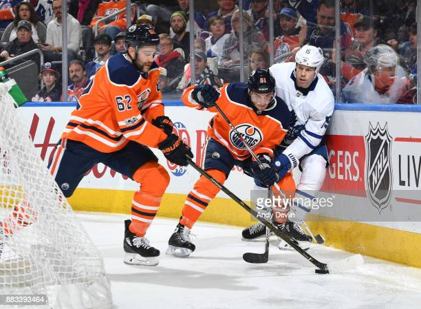 Yohann Auvitu and Eric Gryba of the Edmonton Oilers battle for the puck with Matt Martin of the Toronto Maple Leafs on November 30 2017 at Rogers...