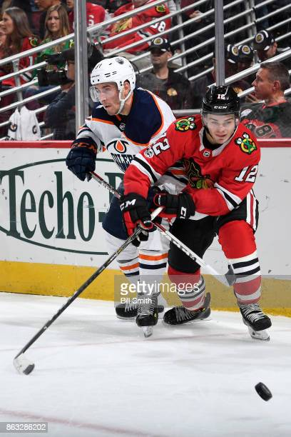 Yohann Auvitu of the Edmonton Oilers and Alex DeBrincat of the Chicago Blackhawks battle for the puck in the third period at the United Center on...