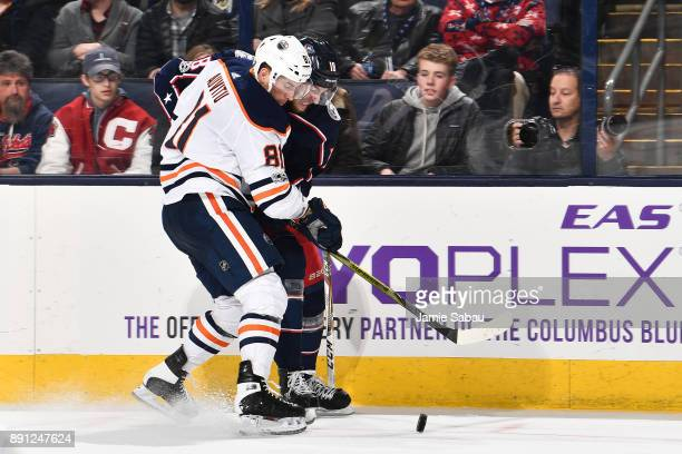 Yohann Auvitu of the Edmonton Oilers and PierreLuc Dubois of the Columbus Blue Jackets battle for a loose puck during the third period of a game on...