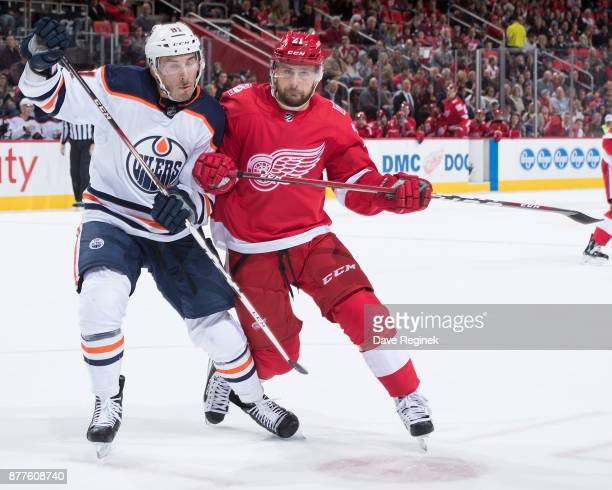 Yohann Auvitu of the Edmonton Oilers fights for position with Tomas Tatar of the Detroit Red Wings during an NHL game at Little Caesars Arena on...