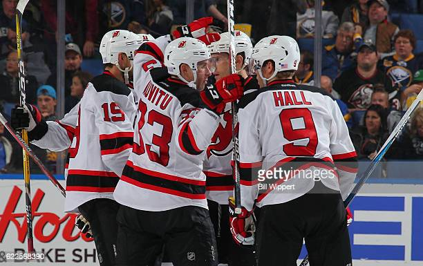 Yohann Auvitu of the New Jersey Devils celebrates his first career NHL goal against the Buffalo Sabres with teammates including Taylor Hall during an...