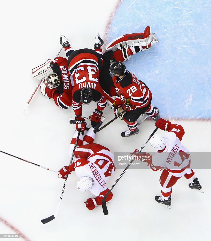 Yohann Auvitu #33 of the New Jersey Devils flies over Cory Schneider #35 during the game against the Detroit Red Wings at the Prudential Center on November 25, 2016 in Newark, New Jersey. The Red Wings defeated the Devils 5-4 in overtime.