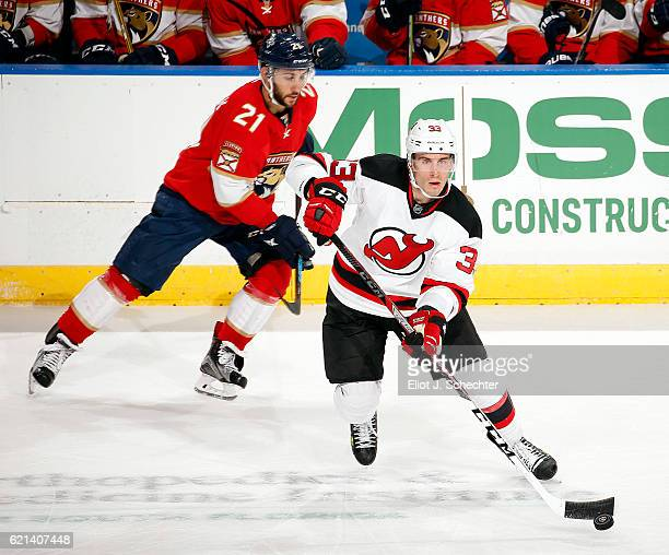 Yohann Auvitu of the New Jersey Devils skates with the puck against Vincent Trocheck of the Florida Panthers at the BBT Center on November 3 2016 in...