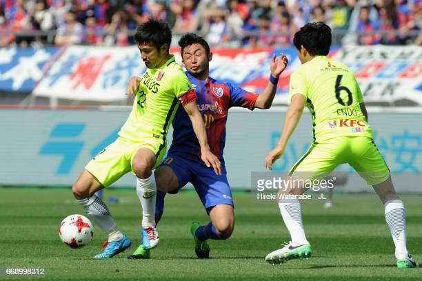 Yohei Kajiyama of FC Tokyo competes for the ball against Yuki Abe and Wataru Endo of Urawa Red Diamonds during the J.League J1 match between FC Tokyo...