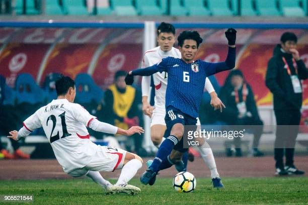Yoichi Naganuma of Japan and Kim Nam-Il of North Korea compete for the ball during the AFC U-23 Championship Group B match between Japan and North...