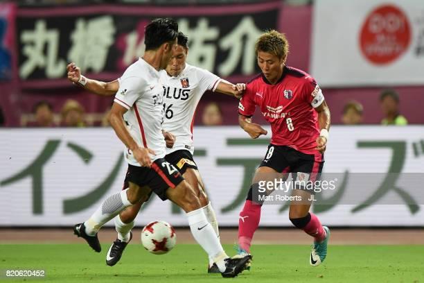 Yoichiro Kakitani of Cerezo Osaka and Ryota Moriwaki of Urawa Red Diamonds compete for the ball during the JLeague J1 match between Cerezo Osaka and...