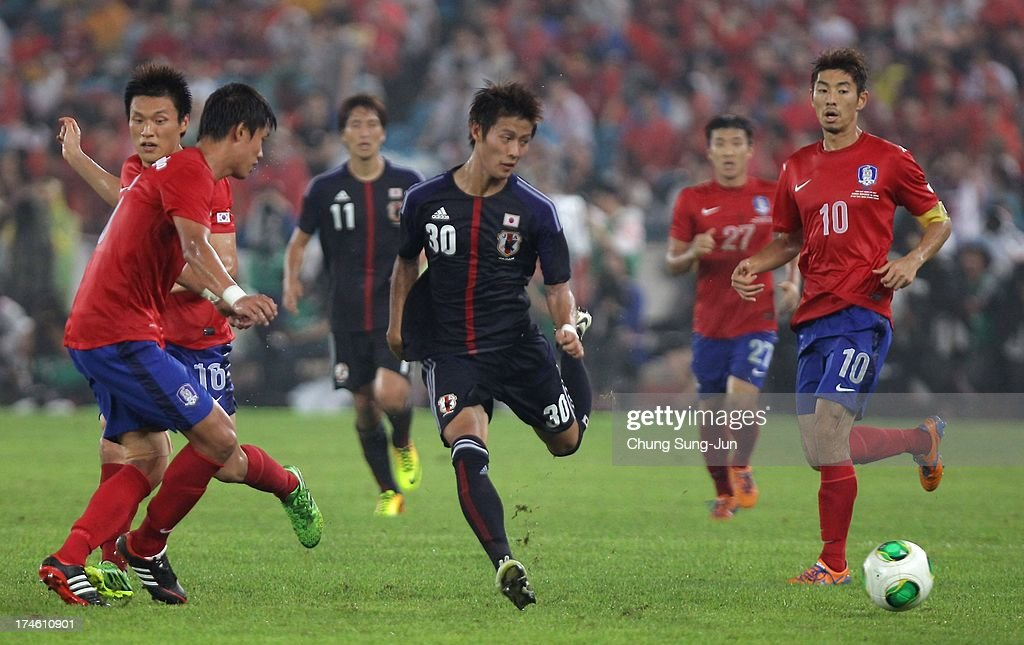 Yoichiro Kakitani (C) of Japan competes for the ball with Lee Myung-Joo (L) of South Korea during the EAFF East Asian Cup match between Korea Republic (South Korea) and Japan at Jamsil Stadium on July 28, 2013 in Seoul, South Korea.