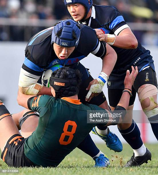 Yoichiro Taniguchi of Tokai Univ Gyosei is tackled by Shota Fukui of Higashi Fukuoka during the 96th National High School Rugby Tournament Final...