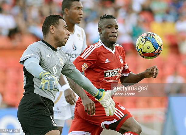 Yoiver Gonzalez of America de Cali struggles for the ball with Carlos Perez goalkeeper of Llaneros FC during a match between America de Cali and...
