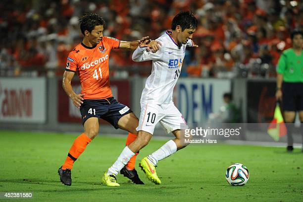 Yojiro Takahagi of Sanfrecce Hiroshima and Akihiro Ienaga of Omiya Ardija compete for the ball during the J. League 2014 match between Omiya Ardija...
