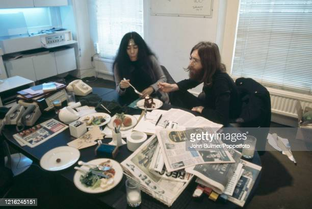 Yoko Ono and john Lennon eating chocolate cake in their office at Apple Records in London circa 1969